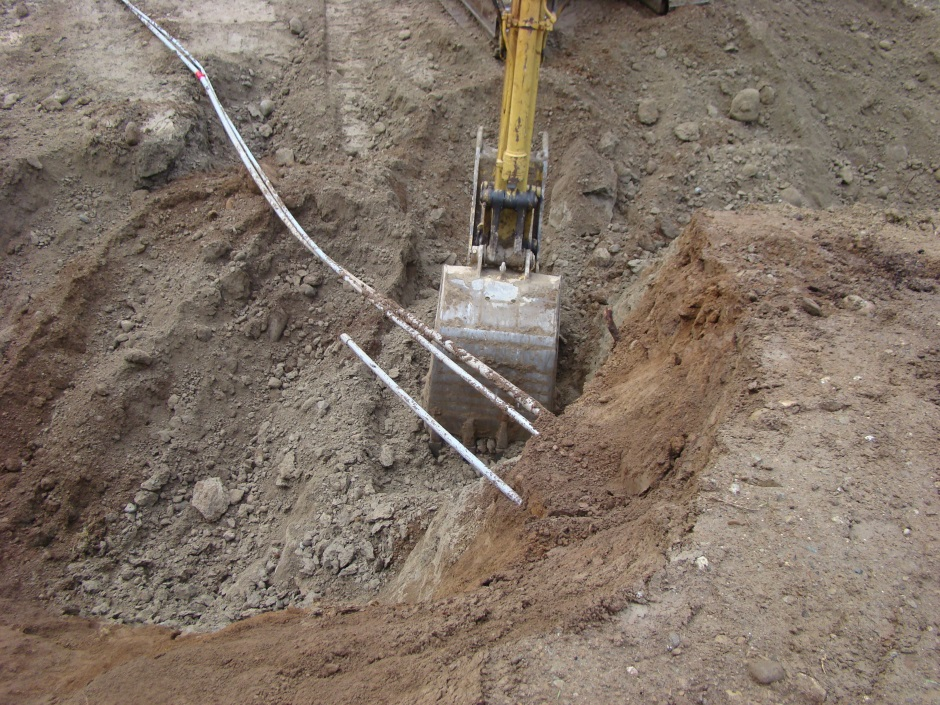 Excavator digging under conduit